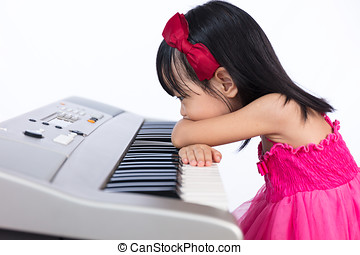 Boring Asian Chinese little girl playing electric piano...