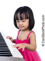 Asian Chinese little girl playing electric piano keyboard in...