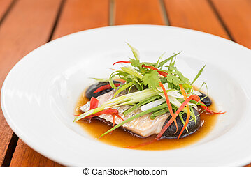 Steamed sea bass fillet with soy sauce and leek in olive...