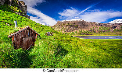 Small mountain hut on grassy hill, Iceland in summer