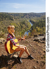 Young blonde woman tourists with guitar on cliff over river...
