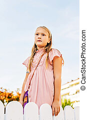 Outdoor portrait of cute 8-9 year old girl wearing pink...
