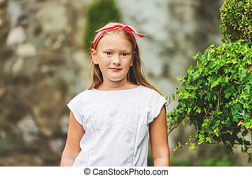 Outdoor portrait of cute 8-9 year old girl wearing red...