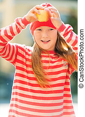 Outdoor portrait of young 9-10 year girl, wearing red stripe...