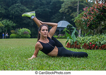 Sporty flexible young woman doing hamstrings stretching...