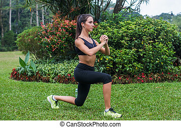 Slim athletic woman working out in park doing knee-bounce...