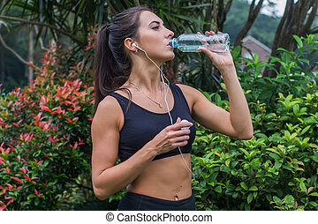 Slim sporty girl drinking water. Fitness young woman taking...