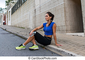 Young athletic female resting after running exercise,...