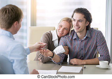 Young happy couple in love getting a key for own apartment,...