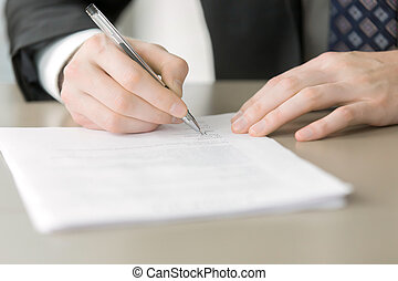 Close up of male hand putting signature in the contract,...