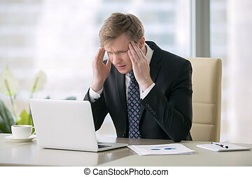 Businessman with headache - Young shocked businessman...