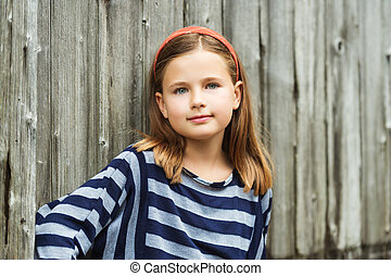 Outdoor portrait of cute little 8-9 year old girl with brown...