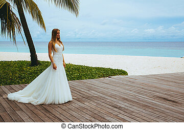 Sexy girl in wedding dress on the seashore on a tropical...