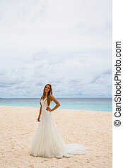Beautiful bride standing alone on a tropical beach by the...