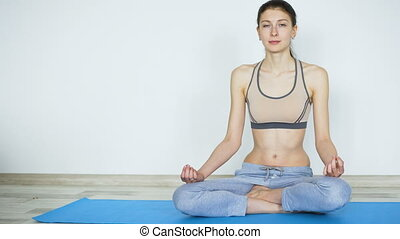 Young woman doing yoga exercise standing still and testing their endurance smile in camera