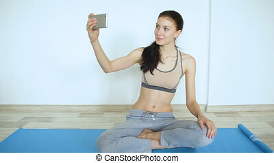 Young woman doing yoga exercise making selfie smile in smartphone
