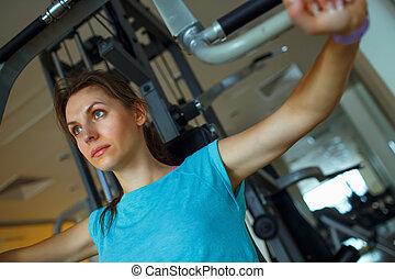 Athletic woman works out on training apparatus in gym