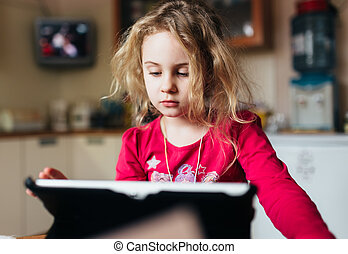 Blonde child girl using tablet computer at home
