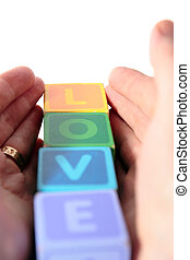 love in toy play block letters held in hands