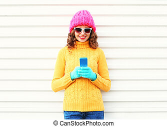 Fashion pretty young smiling woman using smartphone wearing colorful knitted clothes over white background