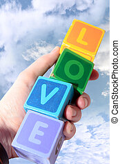 love in wooden play block letters held in hand against clouds