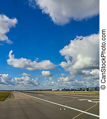Runway Under Puffy Clouds in Airport