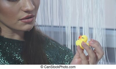 Close-up of fashion model with bright makeup and rubber duck...