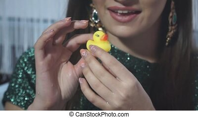 Close-up of a little yellow rubber duck in the hands of the model