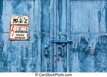 Big industrial metal door with rusty cracked paint