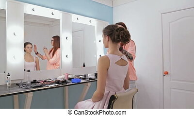 Hair stylist, hairdresser finishing hairstyle for young...