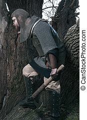 Viking with axe sneaking near the tree