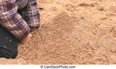 Hands of little boy playing with sand
