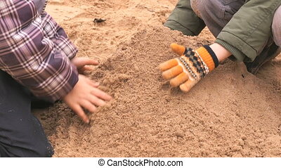 Children playing with sand in outdoor sandbox