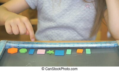 Child learning counting with colors and shapes - Hands of...