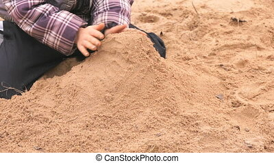 Hands of little kid playing with sand