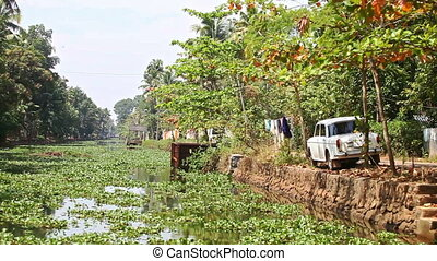 River with Water-plants Car on Bank Linen Dries in Tropics