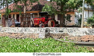 Slow Motion along River Bank with Houses Tractor in Tropics...