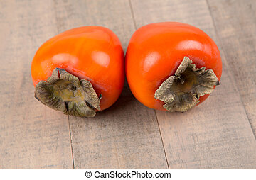 Two whole persimmmons isolated on a wood background