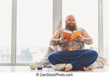Cheerful thick guy enjoying literature