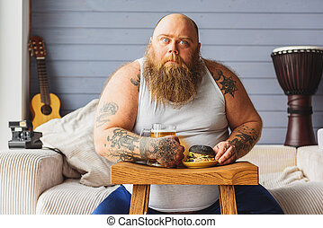 Male fatso drinking alcohol with junk food