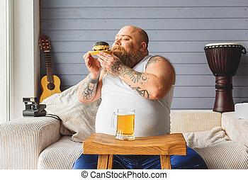 Carefree fat man enjoying smell of hamburger - Happy heavy...