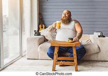 Fat guy relaxing with alcohol drink - Joyful thick man is...