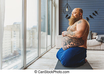 Pensive thick guy resting in apartment - Calm fat man is...
