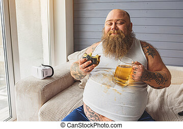Satisfied fat guy enjoying unhealthy food - Happy thick man...