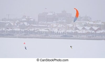 Orange snow-kites on ice river - winter extremal sport at blizzard