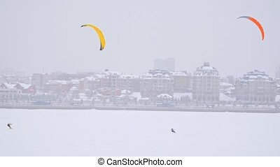 Yellow and orange snow-kites on ice river in front of modern...