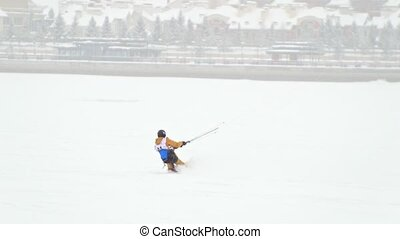 Snow-kite sportsmen in yellow suit rides on the ice river -...