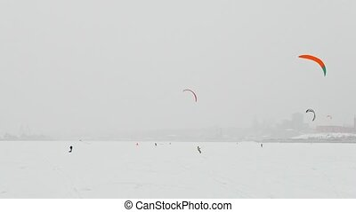 Winter sport - many of snow-kite sportsmen's rides on the ice river at blizzard cloudy day