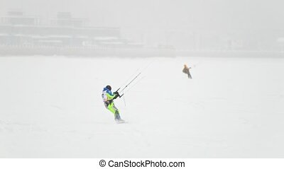 Snow-kite sportsmen in green suit rides on the ice river -...