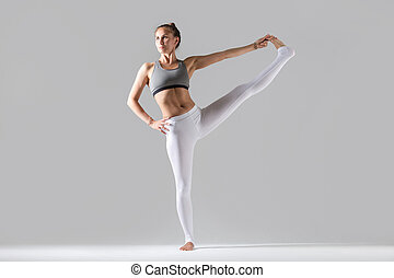 Young woman in Extended Hand to Big Toe pose, studio - Young...
